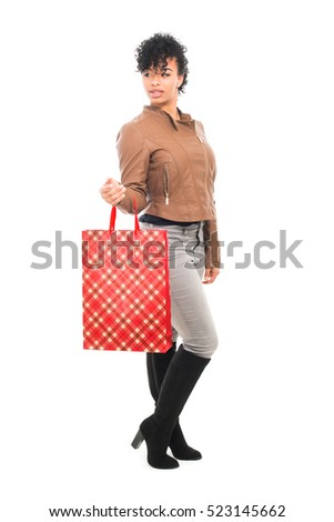 Teenage model with urban fashion clothes carrying a shopping bag isolated on a white background