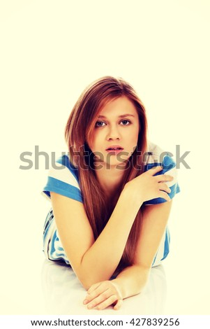 Teenage sad woman lies on the floor - stock photo