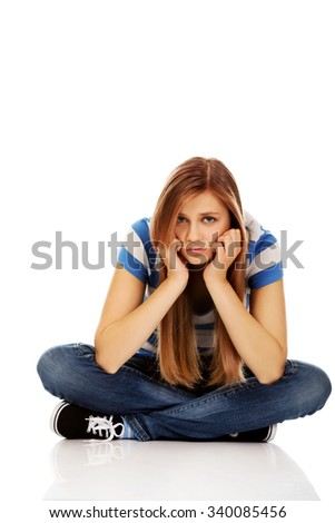 Teenage sad woman sitting on the floor. - stock photo