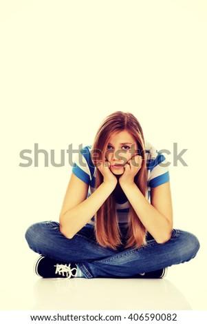 Teenage sad woman sitting on the floor - stock photo