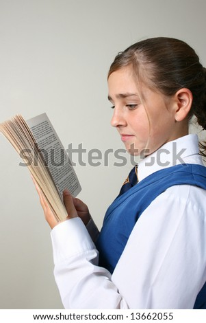 Teenage School girl reading a book, wearing uniform