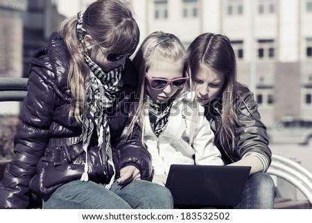 Teenage school girls using laptop on the bench - stock photo