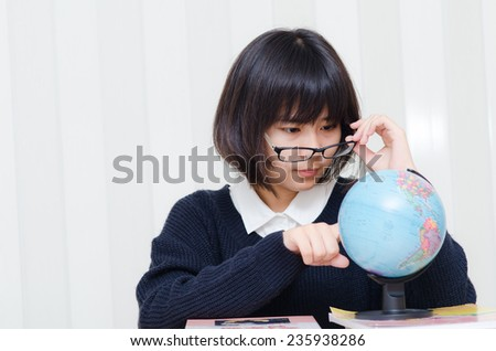 Teenage schoolgirl pointing a place on a globe with her finger - stock photo