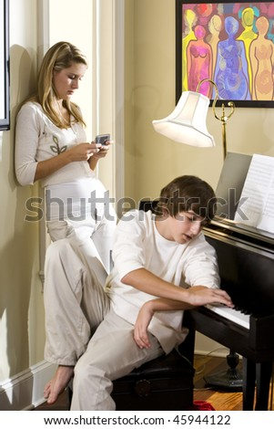 Teenage siblings ignoring each other, one texting, the other playing piano - stock photo