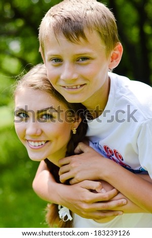Teenage sister and little brother hugging outdoors on summer day green background - stock photo