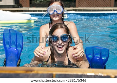 teenage sister playing in the pool - stock photo