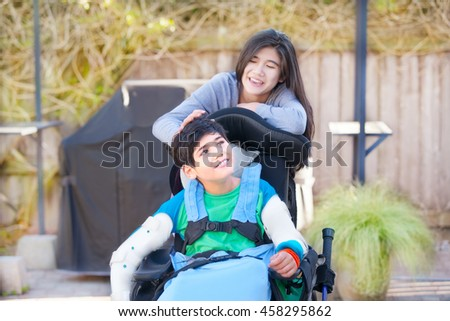 Teenage sister taking care of disabled brother in wheelchair outdoors, laughing and talking - stock photo