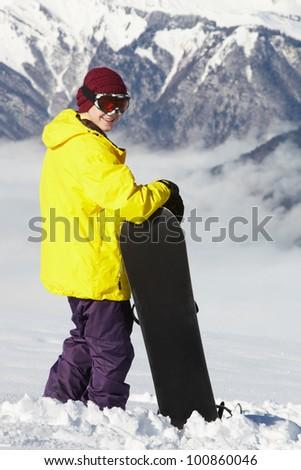 Teenage Snowboarder Admiring Mountain View Whilst On Ski Holiday In Mountains - stock photo