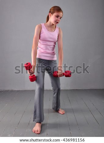 Teenage sportive girl is doing exercises to develop with dumbbells muscles on grey background. Sport healthy lifestyle concept. Sporty childhood. Teenager child exercising with wieghts. - stock photo
