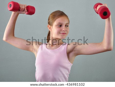 Teenage sportive girl is doing exercises with dumbbells to develop muscles isolated on grey background. Sport healthy lifestyle concept. Sporty childhood. Teenager exercising with weights. - stock photo