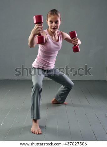 Teenage sportive girl is doing exercises with dumbbells to develop muscles on grey background. Sport healthy lifestyle concept. Full length portrait of teenager child exercising with weights. - stock photo