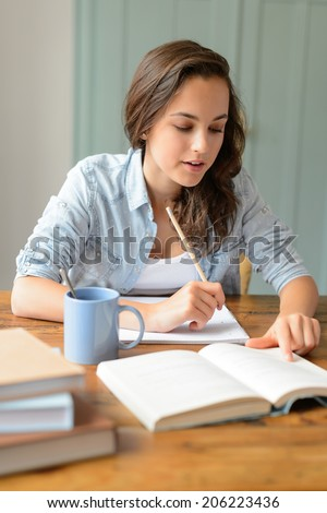 Teenage student girl studying book at home sitting behind table - stock photo