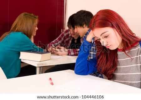 Teenage student not being accepted in the group of her classmates - stock photo