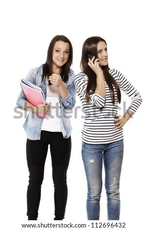 teenage student showing thumb up while her friend is on the phone on white background - stock photo
