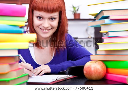 teenage student with red hair, between stacks of books in library