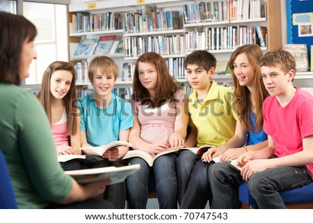 Teenage Students In Library Reading Books With Tutor - stock photo