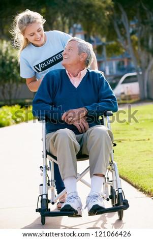 Teenage Volunteer Pushing Senior Man In Wheelchair - stock photo