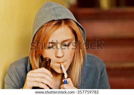 Teenage woman drinking beer and smoking cigarette. - stock photo