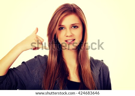 Teenage woman gesturing call me sign - stock photo