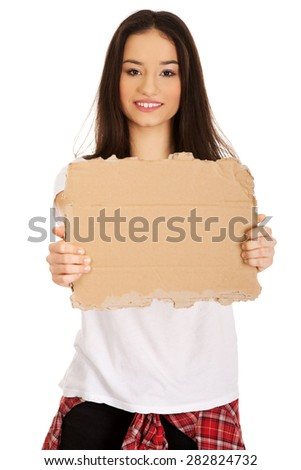 Teenage woman holding empty cardboard. - stock photo