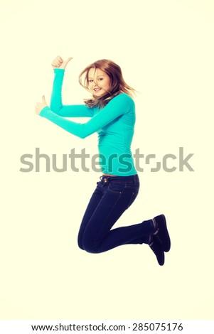 Teenage woman jumping showing thumbs up - stock photo