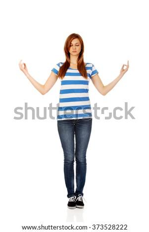 Teenage woman makes meditating gesture - stock photo