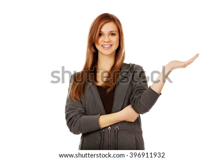 Teenage woman presenting something on open palm - stock photo
