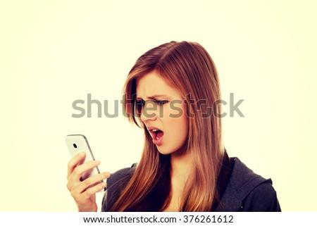 Teenage woman screaming to the phone - stock photo