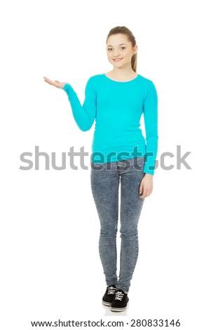 Teenage woman showing something on open hand. - stock photo