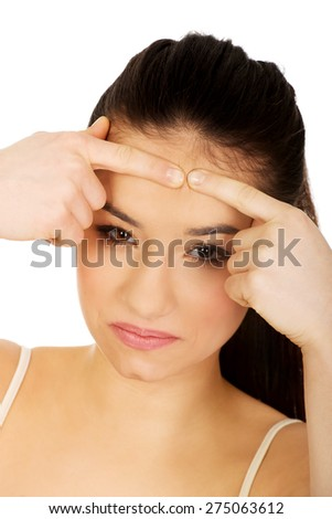 Teenage woman squeezing pimple on forehead. - stock photo