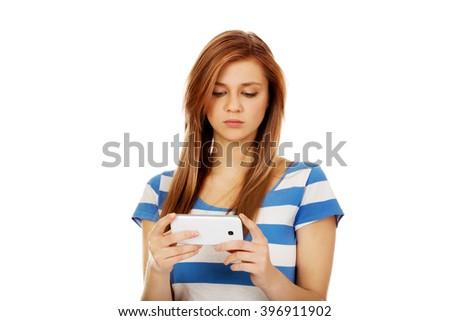 Teenage woman using her smartphone - stock photo
