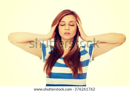 Teenage woman with headache holding her hand to the head - stock photo