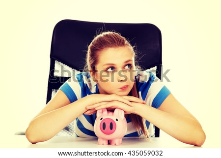 Teenage woman with piggybank on the table - stock photo