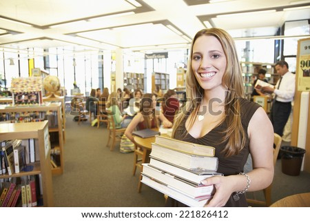 Teenaged girl smiling with stack of books in library - stock photo