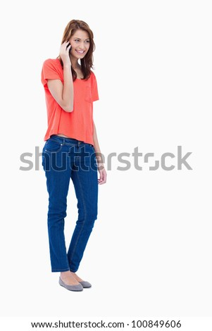 Teenager beaming while using a cellphone - stock photo