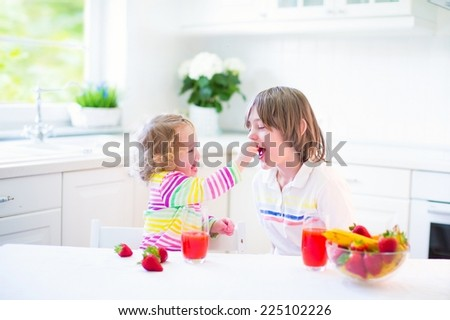 Teenager boy and his funny toddler sister having fruit for breakfast before school and kindergarten drinking juice in a sunny white kitchen with a window  - stock photo