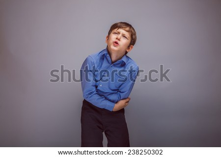 teenager boy brown European appearance holds hands over his stomach on a gray background - stock photo