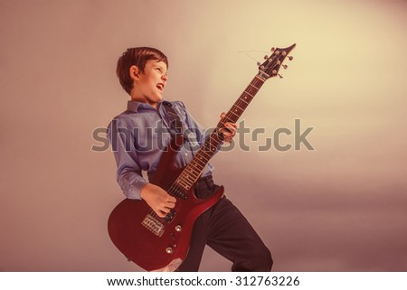 teenager boy brown hair European appearance playing guitar, happy on a gray background retro - stock photo
