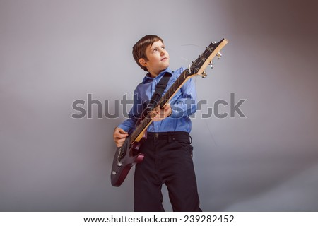 teenager boy brown hair European appearance playing guitar on a gray background - stock photo