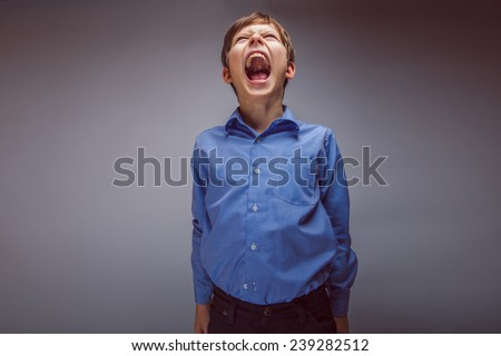 teenager boy brown hair European appearance screams mouth wide open on a gray background - stock photo