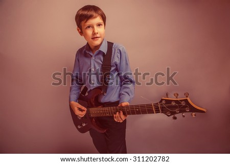 teenager boy brown hair of European appearance playing guitar experiencing happiness retro - stock photo