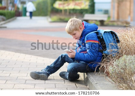 Teenager boy calling on mobile phone sitting outside of the school - stock photo