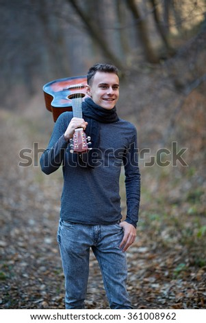 Teenager boy guitar player holding the guitar on his shoulder - stock photo