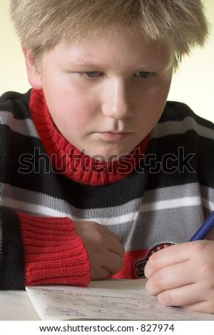 Teenager boy handwriting his homework - stock photo