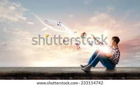 Teenager boy in jeans and shirt reading book