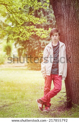 teenager boy leaning against a tree in a park. - stock photo