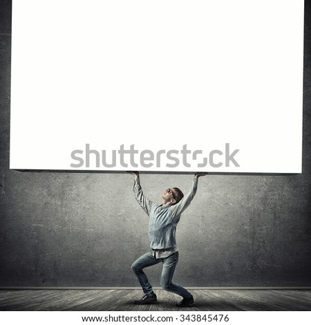 Teenager boy lifting up white blank banner. Place for your text - stock photo
