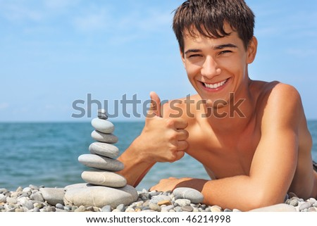 teenager boy lying on stony seacoast, creates pyramid from pebble, shows ?? gesture - stock photo