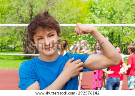 Teenager boy shows bicep muscles on the playground - stock photo
