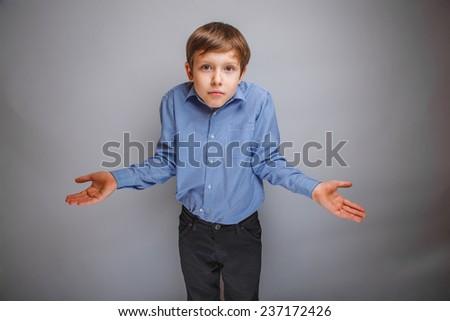 teenager boy shrugs at a loss - stock photo